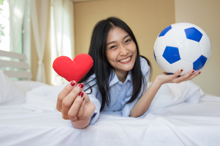Woman is playing with a soccer ball in the bedroom.