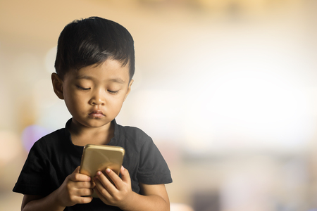 Asian Boy 2 years old playing smartphone in blurred background.Selective focus