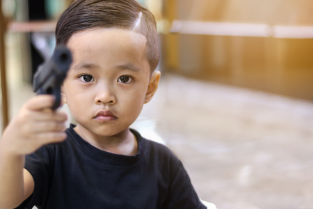 Asian boy playing toy gun. Stock Photo