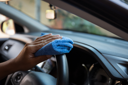 Close up of human hand are cleaning in a car.