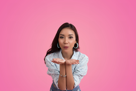 Happy Asian woman on pink background Stock Photo