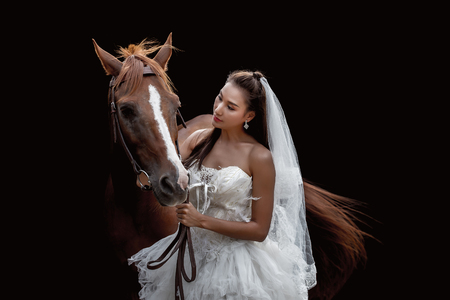 Beautiful bride with horse on black background