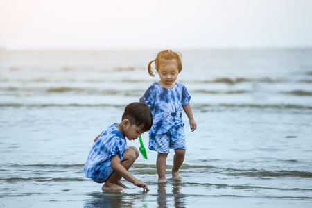 Happy boy and girl playing on the beach.