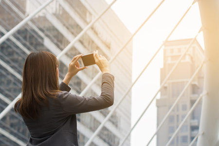 Young woman using camera in smart phone for shooting photo in urban background Stock Photo