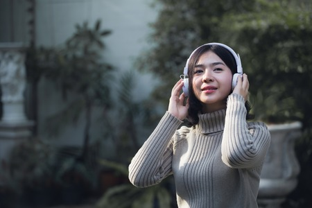 Happy Asian girls are listening to music in the park.