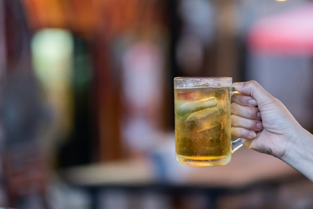 Human hand holding a glass of beer on bokeh background. Stock Photo