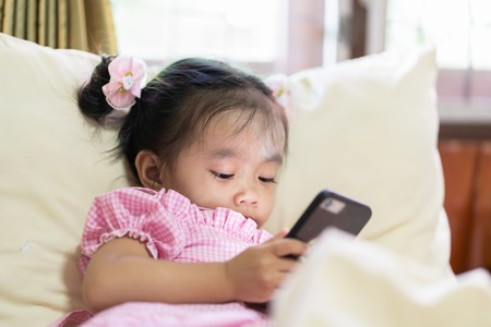 Asian baby girl looking at smart phone on the bed