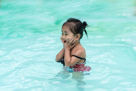 Happy baby Asian girl in swimming pool