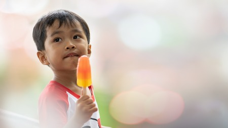 Asian boy eating ice cream in blurred background