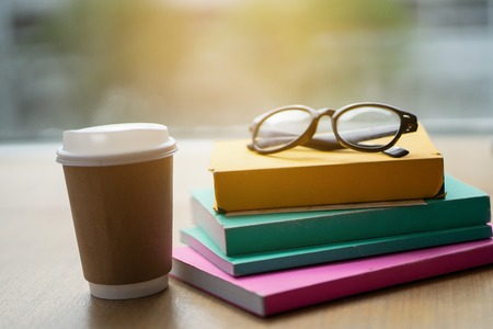 Many books are put on the table with coffee.