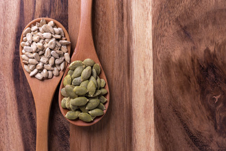 Top view of Sunflower seeds and pumpkin seeds in wooden spoon
