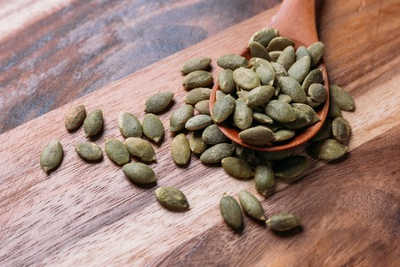 Pumpkin seeds in a wooden spoon Stock Photo