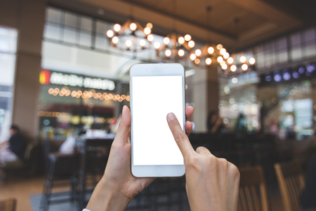 Hand using smart phone in blurred images in the coffee shop for background Stock Photo