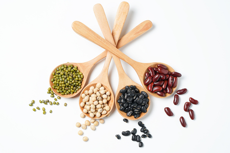 Many nuts and sesame seeds on wooden spoon on white background. Stock Photo