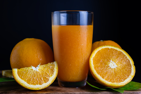 Glass of orange juice with fresh fruits on wooden floor