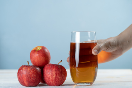 Hand holding Fresh apple juice in the glass