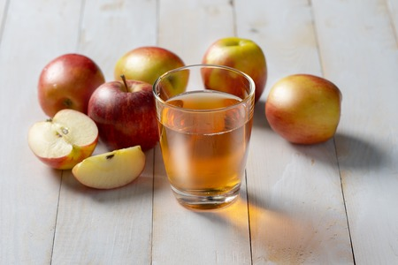 Fresh apple juice in the glass on wooden floor.
