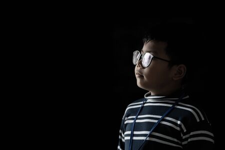 Asian boy in black background.