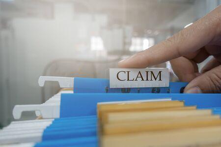 Die menschliche Hand holt das Anspruchsdokument in der Datei für den Kunden an das Versicherungsunternehmen. Versicherungskonzept ab.
