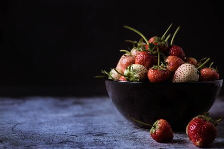 Strawberry fresh berries in a bowl of black. Strawberry's antioxidants.