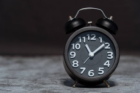 Black Alarm clock on concrete background