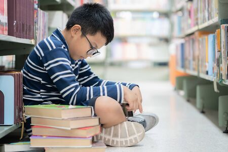 Asian boy reading a book in the library.