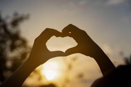 human hands in heart shape framing in sunset