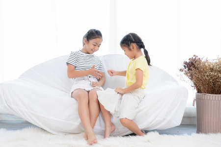 Asian girls playing together in a white room