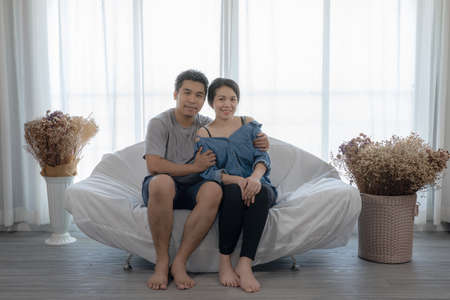 Happy Asian couple sitting at the sofa