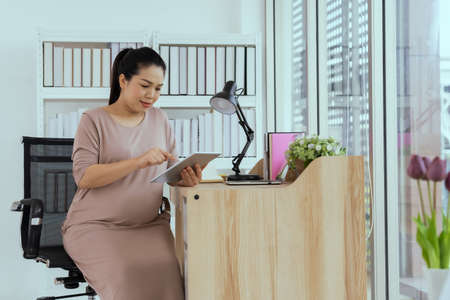 Asian pregnant women are working with tablets and laptops.