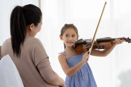 The daughter playing violin for her mother to listen. 版權商用圖片