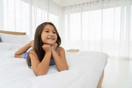 Asian girls on a white bed are happy. 免版税图像