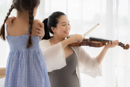 Mom plays violin for her daughter to listen. 版權商用圖片