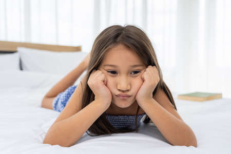 Asian girl on a white bed are sad and unhappy.