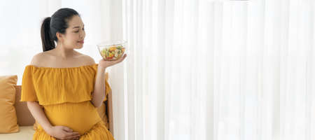 Beautiful Asian pregnant women are enjoying eating fruit and vegetable salads. 版權商用圖片