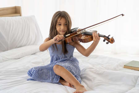 Asian girls on a white bed are colored violin