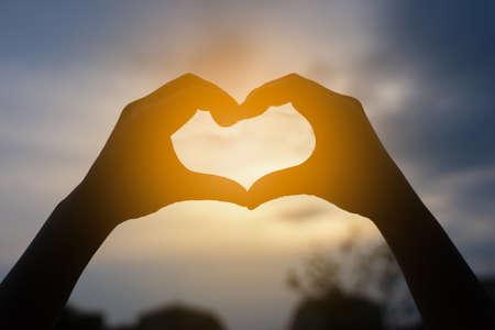 human hands in heart shape framing in sunset Stockfoto
