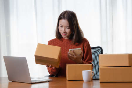 Beautiful Asian girl shop online are writing the customer's address down to the delivery box.