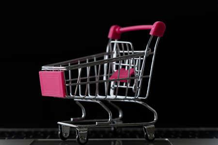 Shopping cart on laptop keyboard for e-commerce business concept.black background 免版税图像