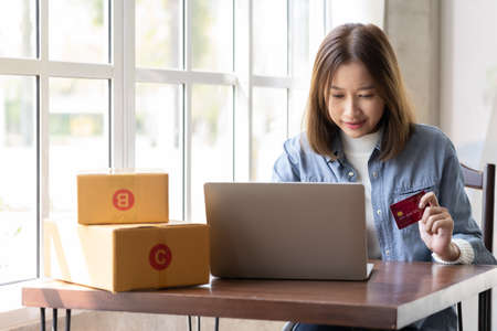 Happy Asian woman shopping online and paying by credit card.technology and ecommerce concept