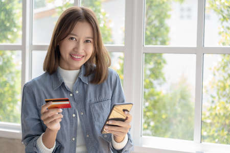 Beautiful Asian women are buying products online and paying with credit cards.