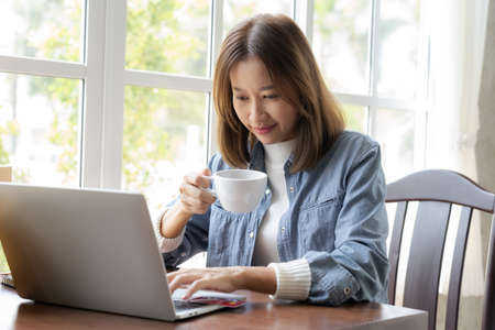 Happy Asian woman shopping online and paying by credit card in coffee shop. technology and ecommerce concept 免版税图像