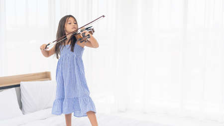 Happy Asian Girl are playing violin in the white room.