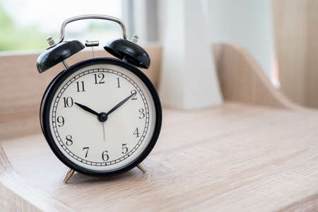 Vintage Black Alarm clock on table in bedroom 免版税图像