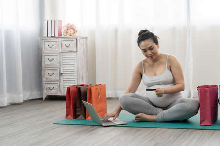 Pregnant women are shopping online for baby products.technology and ecommerce concept.