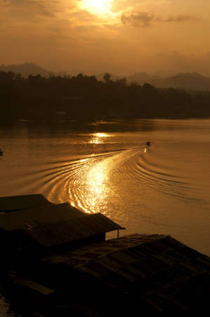 Golden sunset light, and a long tail boat through the river. photo
