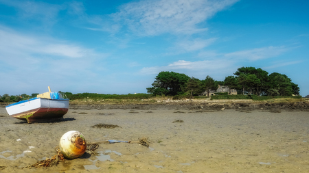 Fisherman boat resting in the sand near old stone house on an island Stock Photo