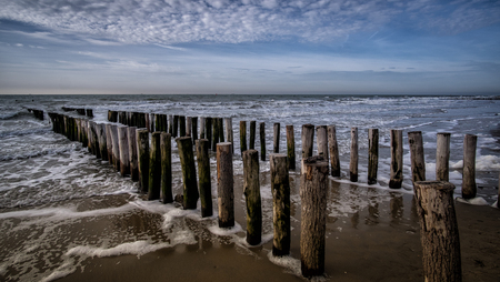 Pier during sunny weather with clouds at the beach in Vlissingen, Zeeland, Holland, Netherlands Stock Photo