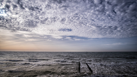 The wooden pier at the beach with cloudy blue sky in Vlissingen, Zeeland, Holland, Netherlands