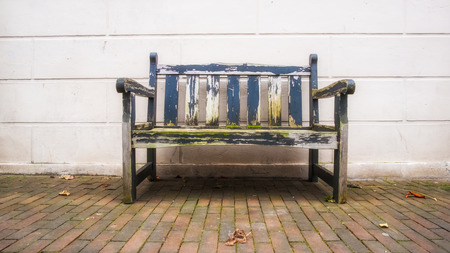 Used old bench in front of white wood wall standing on cobblestone in urban area
